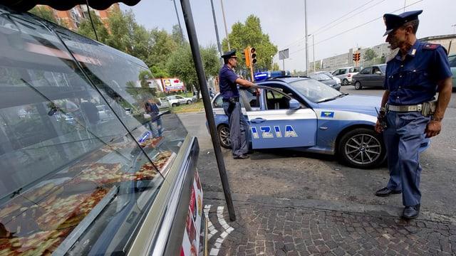 Zwei Polizisten stehen vor einem Polizeiauto auf der Strasse in Neapel.