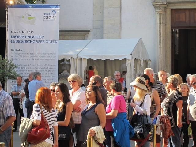 Gut ein Dutzend Personen stehen vor der Oltner STadtkirche, dazwischen ein Plakat welches die Eröffnungsfeier ankündet und mehrere Zelte.