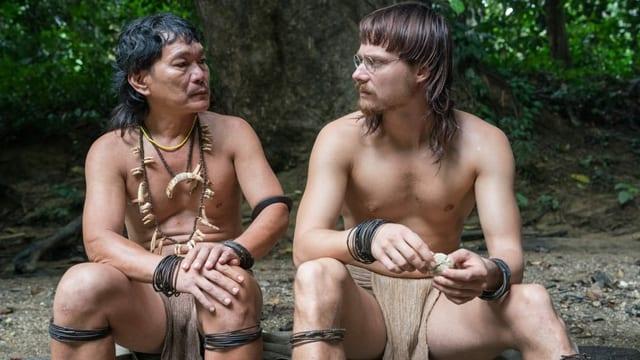 Filmstill: Zwei kaum bekleidete Urwaldbewohner sitzen nebeneinander.
