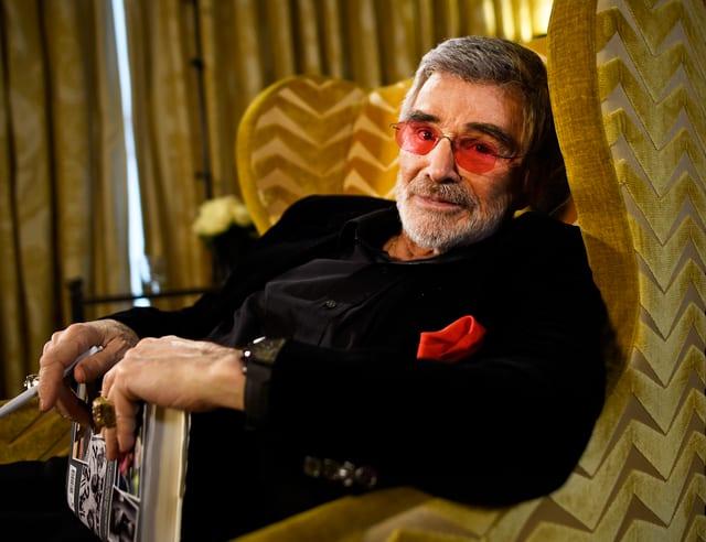 Burt Reynolds liegt auf einem Sofa und trägt eine Sonnenbrille mit roten Gläsern.