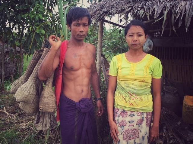 Fischer Phyo Win mit seiner Frau vor seiner Bambushütte.