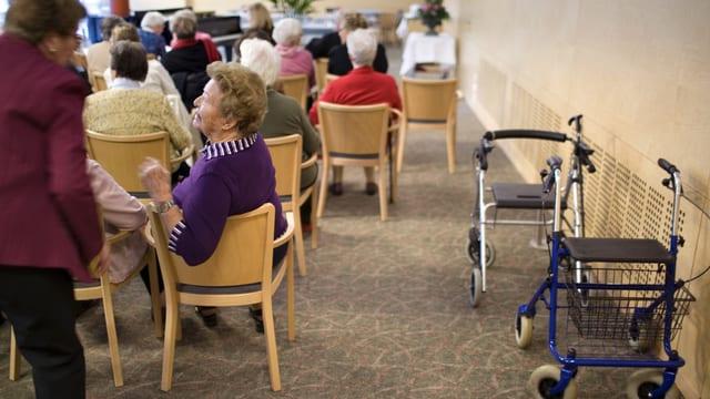 Ältere Menschen in einem Raum, auf der rechten Seite stehen Rolatoren