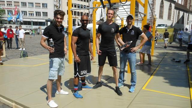 Vier Sportler in schwarzen T-Shirts posieren vor einem gelben Klettergerüst.
