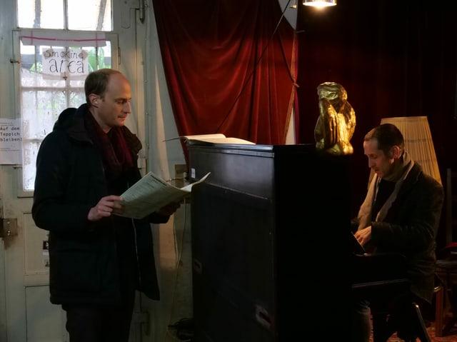 Ein Mann spielt Klavier, ein anderer singt.