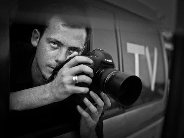 Porträt von Rémi Ochlik mit seiner Kamera.