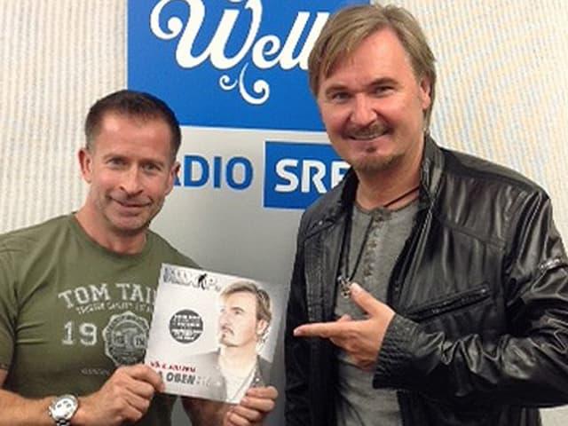Nik. P. zeigt mit Finger auf Leonard und seine CD.