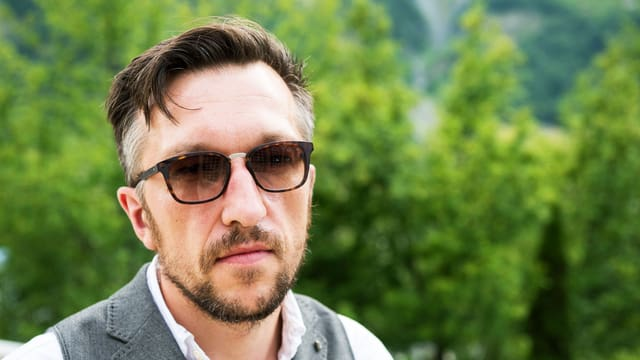 Lukas Bärfuss trägt eine Sonnenbrille.