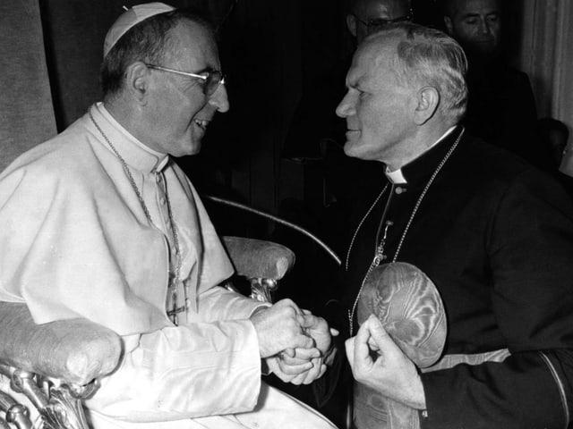Papst Johannes Paul I. und sein Nachfolger Karol Wojtyla schütteln sich die Hände.