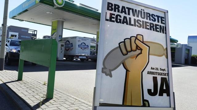 Tankstelle mit Plakat, auf dem «Bratwürste legalisieren» steht
