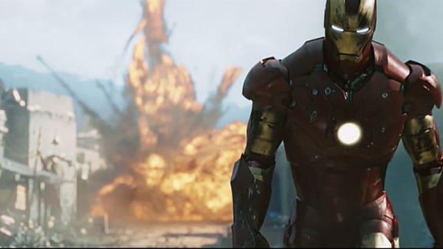 Im Vordergrund rechts ein Mann in eisernem Anzug mit Helm, der sein Gesicht verdeckt. Die schlitzförmigen Augenlöcher läuchten, ausserdem auch ein Punkt auf der Brust. Im Hintergrund der Feuerball einer Explosion.