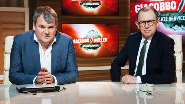 Mike Müller in weissem Hemd und blauem Blazer und Viktor Giacobbo in weissem Hemd, Kravatte und dunklem Blazer sitzen an einem Blanken Tisch. Sie blicken den Betrachter an. Im Hintergrund zu sehen: Das Logo der TV-Sendung «Giacobbo / Müller».