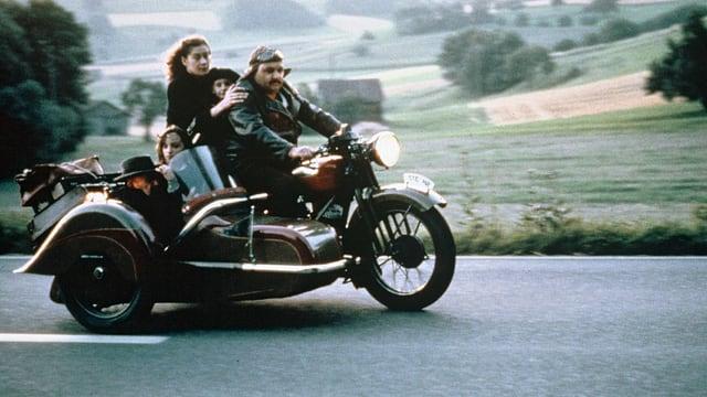 Ein Mann fährt auf einem Motorrad mit Seitenwagen. Darin ist eine Frau, ein älterer Mann und zwei Kinder.