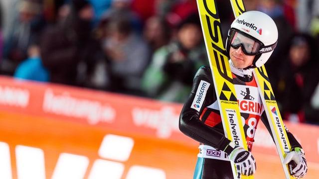 Simon Ammann steht mit seinen Ski im Zielraum.