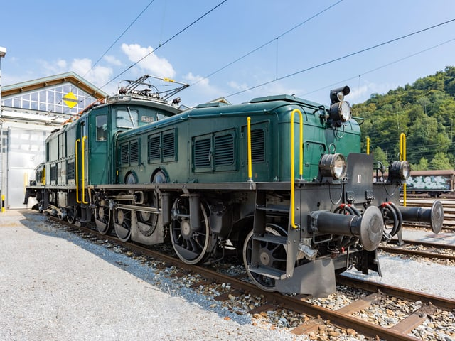 Grüne Lokomotive auf dem Gleis.