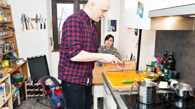 Ein Mann kocht in der Küche, die Frau sitz mit Baby am Tisch