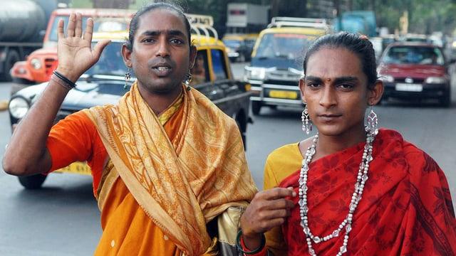 Zwei indische Männer in Frauenkleidung stehen am Strassenrand.
