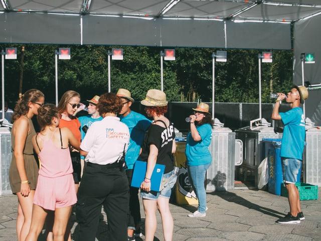 Menschen diskutieren beim Eingang mit der Security