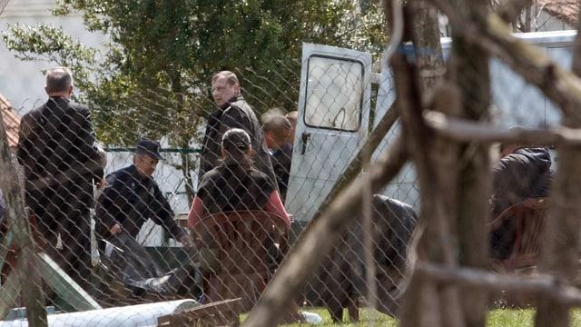 Sicherheitskräfte tragen eine Leiche weg.