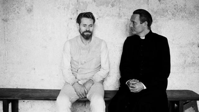 zwei Männer sitzen auf einer Bank