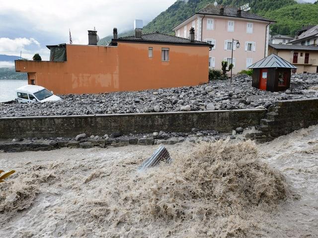 Ein Strasse voller Geröll. Im Vordergrund der Fluss mit einem hohen Wasserpegel.