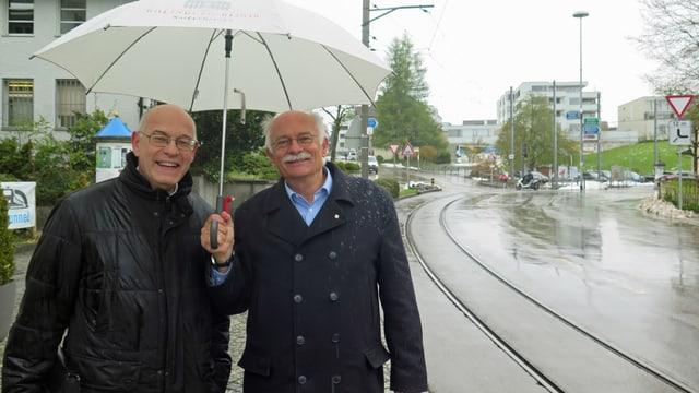Zwei Männer unter einem Regenschirm lachen in die Kamera.