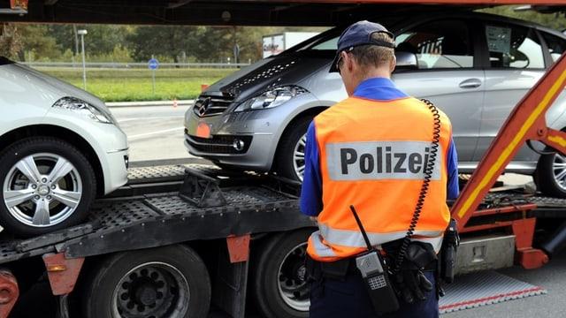 Ein Polizist kontrolliert einen Lastwagen mit Autos.