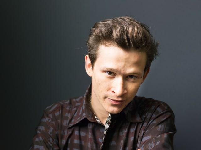 Ein junger Mann mit braunen Haaren und dunklem blickt in die Kamera.