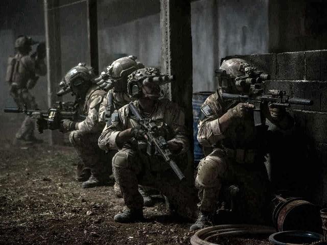 Soldaten in Deckung mit Maschinengewehren in Position.