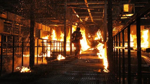 Ein Mann geht in einem brennenden Hochhaus auf die Flammen zu.