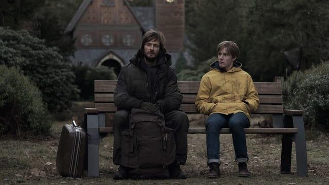 Ein Mann mit einem grossen Rucksack und ein Junge im gelben Regenmantel sitzen auf einer Bank.
