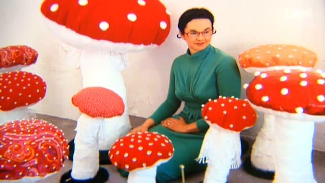 Ivana Falconi in einem grünen Kleid zwischen vielen, unterschiedlich grossen Fliegenpilzen aus Stoff und andferen Materialien.