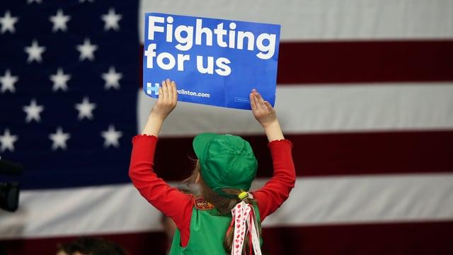 Ein Mädchen hält ein Schild mit der Aufschrift «Fighting for us» in die Höhe.