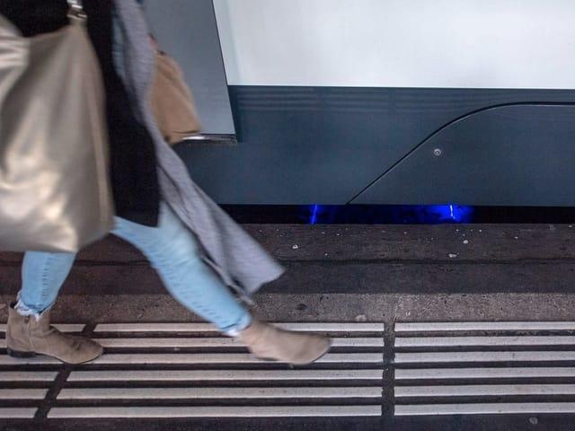 Eine Frau läuft neben einem Zug, der blaue Messsensor strahlt unter dem Zug hervor.