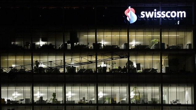 Mehrstöckiges, transparentes Gebäude mit Swisscom-Logo: Es ist dunkel und in den Büros wird gearbeitet.