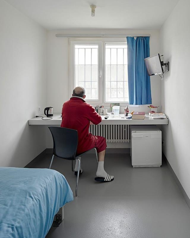 Ein Gefängnisinsasse im roten Mantel.