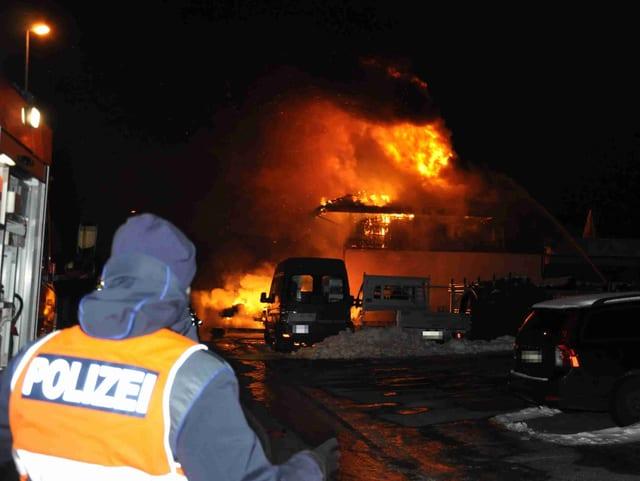 Ein Poliziste vor einem brennenden Haus