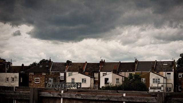 Reihenhäuser, dahinter dunkle Wolken
