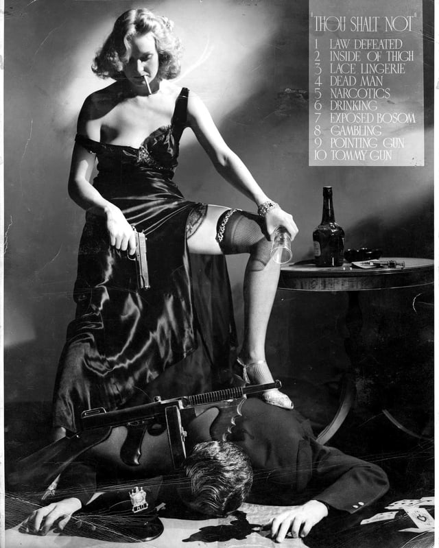 Eine Frau steht mit einem Bein auf einem Mann, der am Boden liegt. Zigarette im Mund, Gewehr am Boden, ein Pistole in der Hand.
