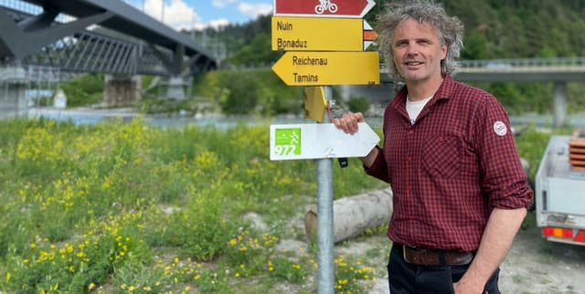"Stephan Kaufmann, manader da biro da l'uniun ""Wanderwege Graubünden"" avant ina pitga cun mussavias mellens, per viandar, ed in alv cun si Schiessanlage Nulez."