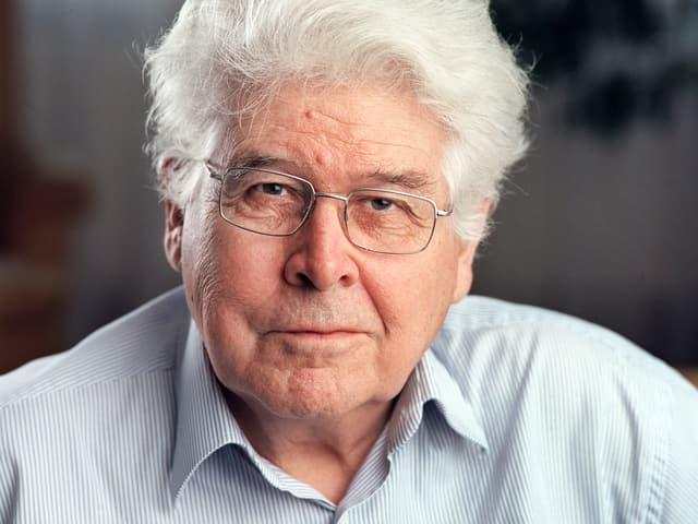 Porträt eines älteren Mannes mit Brille und weissen Haaren.
