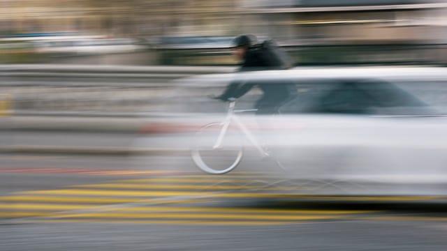 Fussgängerstreifen über den ein Auto und ein Velo flitzen (unscharf)