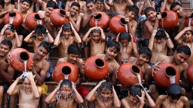 Studenten in Indien begiessen sich gegenseitig mit Wasser aus Krügen.