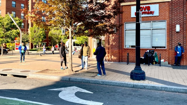 Junge, arbeitslose Männer treffen sich vor der Apotheke; Obdachlose betteln um Geld oder Essen.