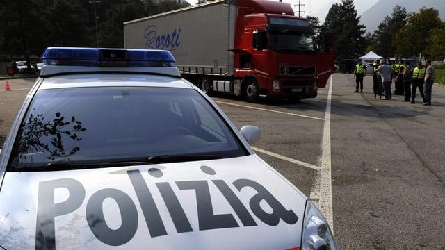 Auto der Tessiner Kantonspolizei vor einen Lastwagen. Dahinter einige Polizeiautos.