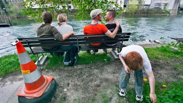 Ein hetero- und ein homosexuelles Paar sitzen auf einer Bank, davor spielt ein Kind.