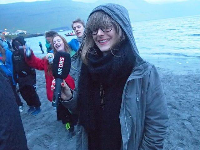 SRF 3 - Moderatorin Tina Nägel steht mit einem Mikrofon am Strand. Sie trägt eine Jacke mit Kapuze. Ihr Haar ist vom Wind verweht.