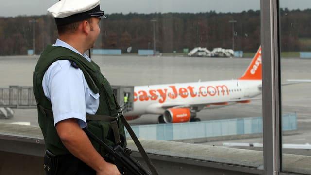Ein bewaffneter Polizist am Flughafen, im Hintergrund ein Easyjet-Flugzeug.