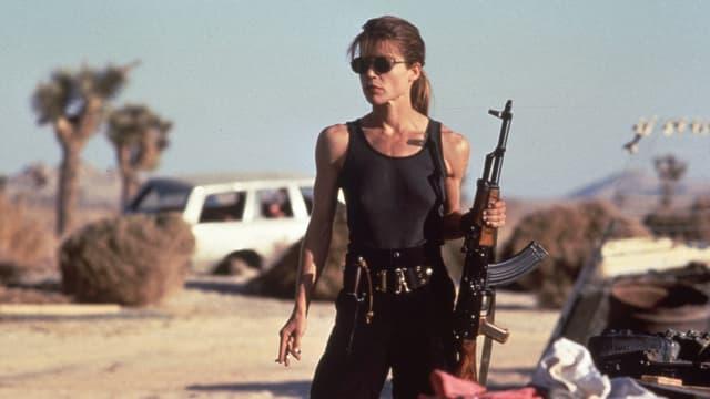 Eine junge bewaffnete Frau mit Sonnenbrille.
