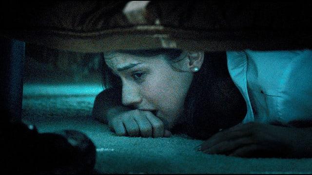 Die Tochter versteckt sich zitternd unter dem Bett, während der Eindringling ins Zimmer tritt.