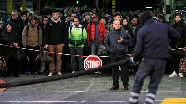 Zahlreiche Flüchtlinge stehen hinter einer Kette mit einem Stopp-Schild daran. Vorne zwei Beamte.